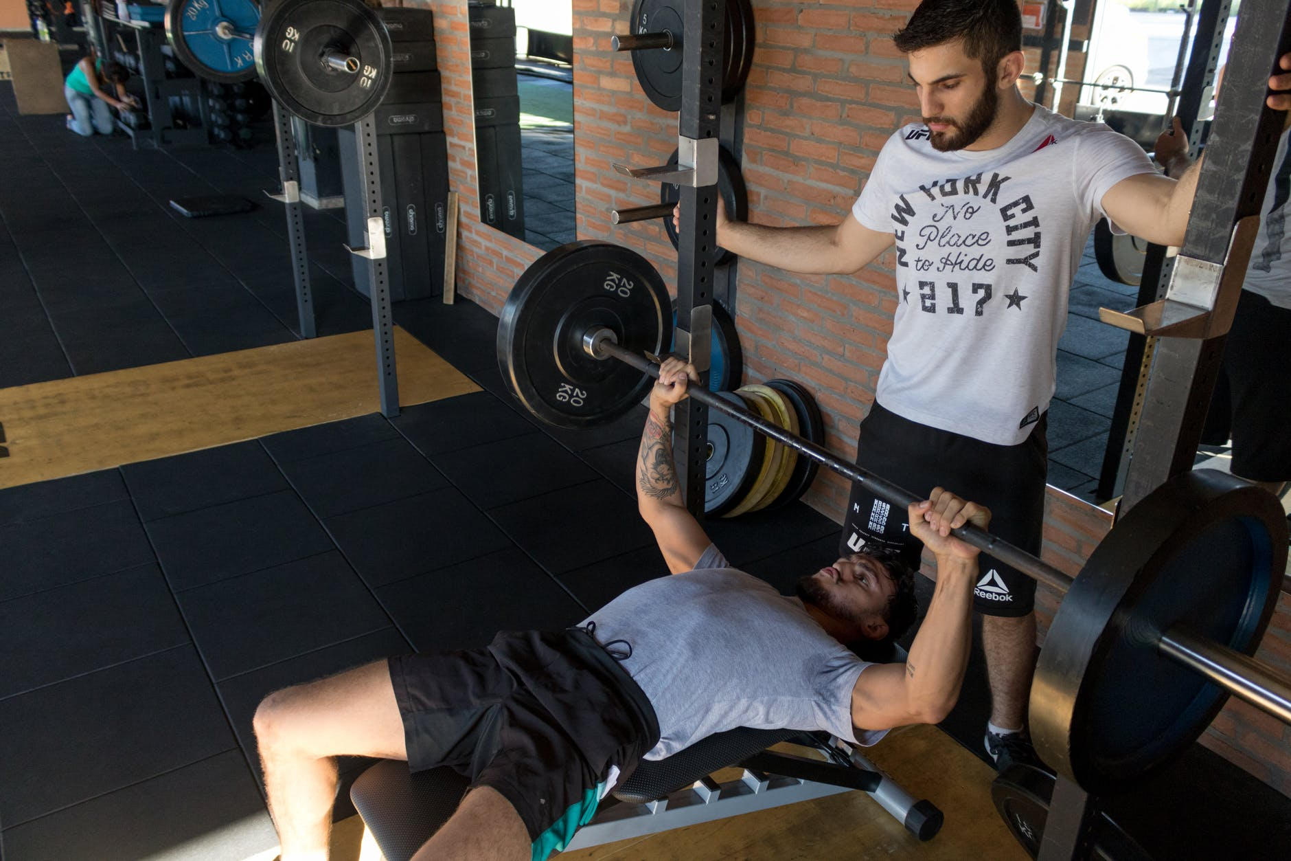 man lying while doing barbell